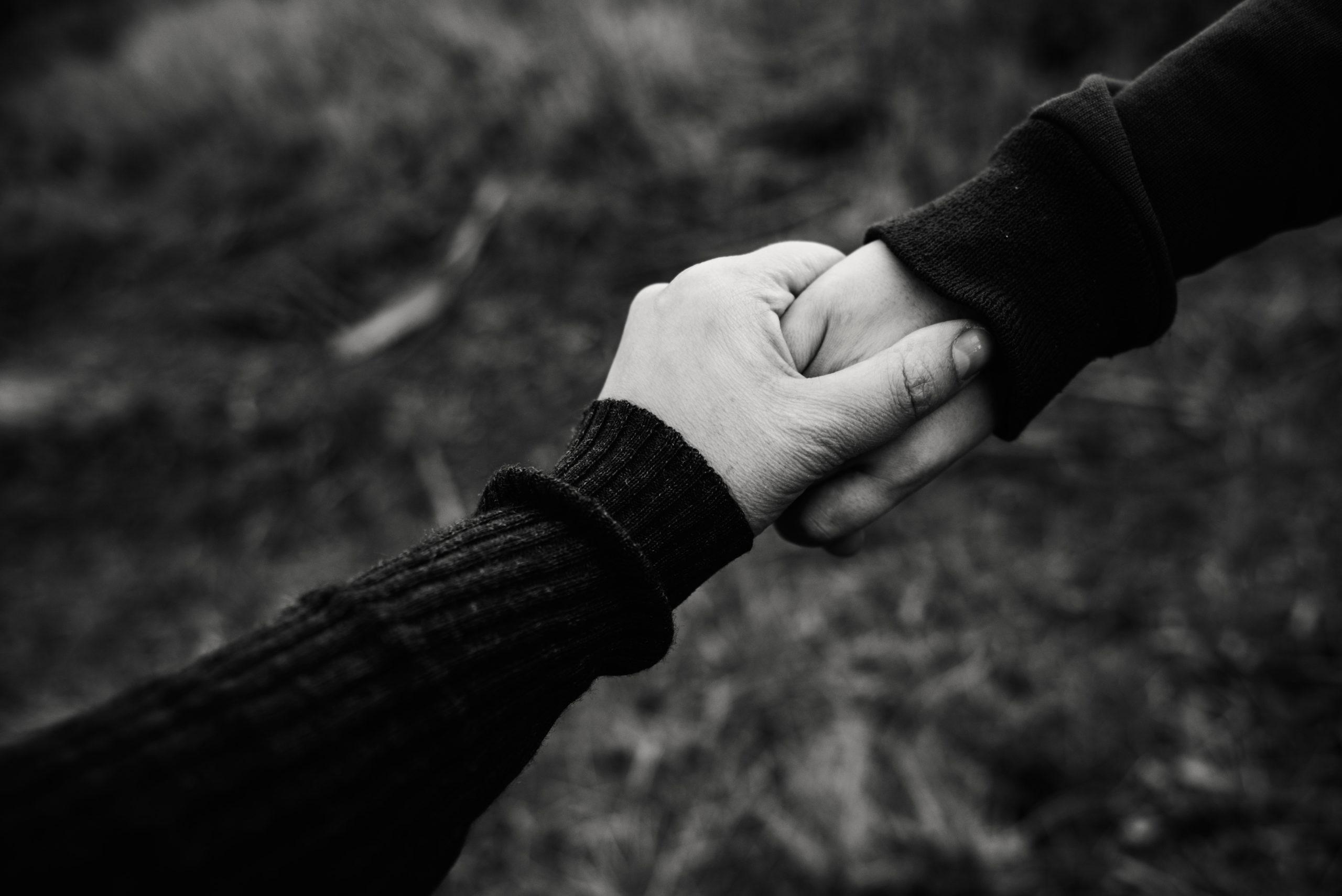 deux personnes se tenant par la main en soutien en noir et blanc -roco